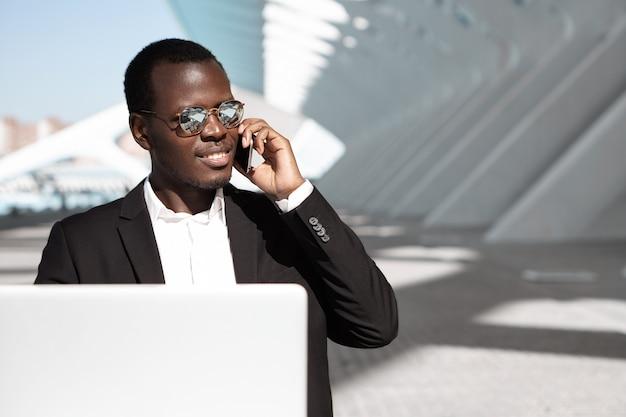 Glimlachende zwarte zakenman in formele slijtage en spiegelzonnebril die bij openlucht stedelijke koffie met laptop computer zitten terwijl het spreken op mobiele telefoon. mensen, zaken en moderne technologie