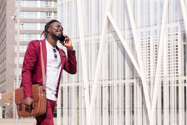 Glimlachende zwarte zakenman met aktetas loopt door het financiële centrum van de stad pratend over telefoon, concept van technologie en communicatie, kopieer ruimte voor tekst