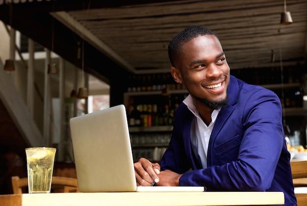 Glimlachende zwarte zakenman met laptop bij koffie