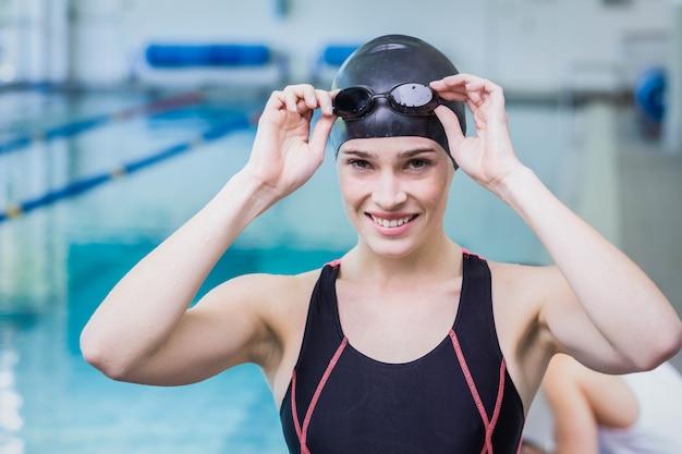 Glimlachende zwemmer die de camera op het vrije tijdscentrum bekijkt