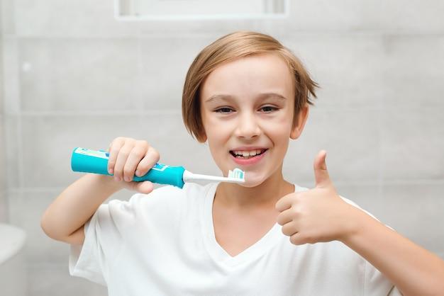 Glimlachjongen geeft om de gezondheid van zijn tanden. kid tandenpoetsen met elektrische borstel in de badkamer. elke dag mondhygiëne. gezondheidszorg, kindertijd en mondhygiëne. gelukkige jongen die tanden schoonmaakt.