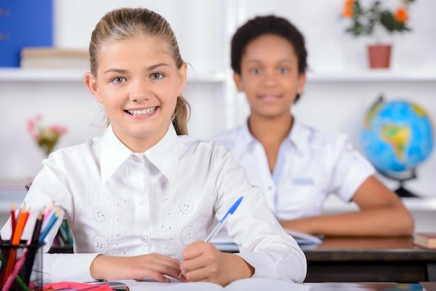 Glimlachleerlingen glimlachen op school in de klas.
