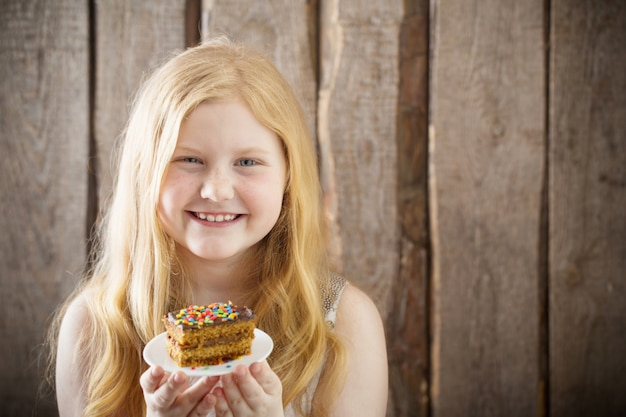 Glimlachmeisje met cake op houten muur