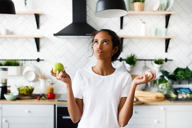 Glimlachte aantrekkelijke mulatvrouw denkt over een appel met dolkomisch gezicht en kijkt naar de bovenkant op de witte moderne keuken
