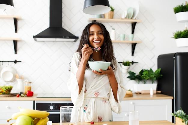 Glimlachte aantrekkelijke mulatvrouw eet gesneden fruit op witte moderne keuken gekleed in nachtkleding met rommelig los haar en kijkt recht