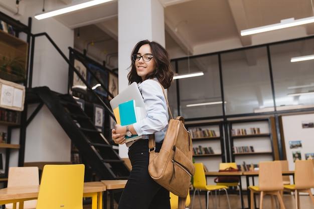 Glimlachte brunette jonge vrouw in zwarte bril wandelen met werkspullen en laptop in bibliotheek. slimme student, universiteitsleven, glimlachend