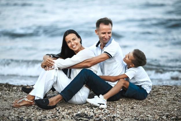 Glimlachte familie zit op het rotsachtige strand in de buurt van de stormachtige zee en knuffelen, ouders en kind