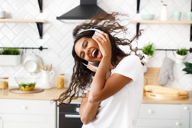 Glimlachte hilarische mulatvrouw met rommelig haar in grote draadloze hoofdtelefoons danst gelukkig met haar geopende mond in de moderne keuken