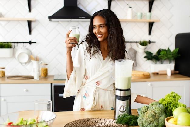 Glimlachte mooie mulatvrouw houdt groene smoothie dichtbij de lijst met verse groenten op witte moderne keuken gekleed in nachtkleding met los haar en kijkt op het glaswerk