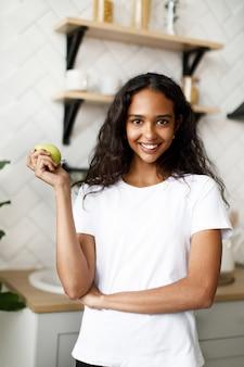 Glimlachte mulatvrouw gekleed in wit t-shirt, met mooi gezicht en los haar houdt groene appel in de hand in de keuken