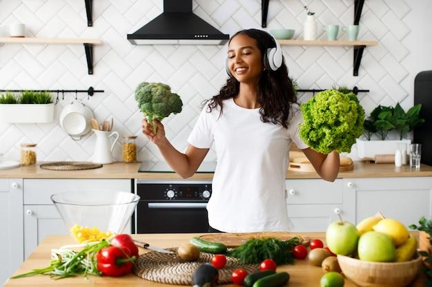 Glimlachte mulatvrouw in grote draadloze hoofdtelefoons glimlacht en houdt salade en broccoli op de moderne keuken dichtbij tafel vol met groenten en fruit