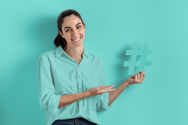 Glimlachvrouw die het hashtag teken houden