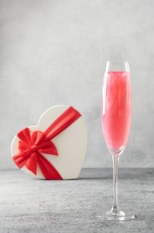 Glinsterende eetbare glitter mousserende wijn in twee glazen met geschenk in de vorm van hart op grijs.