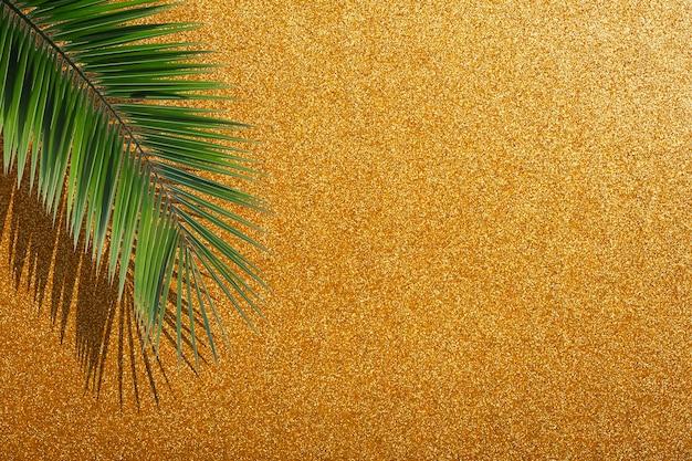 Glitter gouden achtergrond. gouden feestelijke heldere glamoureuze achtergrond met tropische palmbladeren en glanzende sparkles. hoge kwaliteit foto