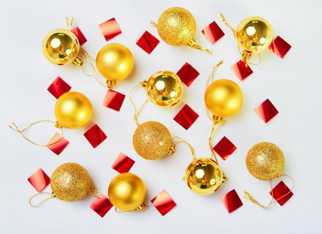 Glitter gouden kerstballen en stukjes van een rood lint op een witte ondergrond. plat leggen. bovenaanzicht.