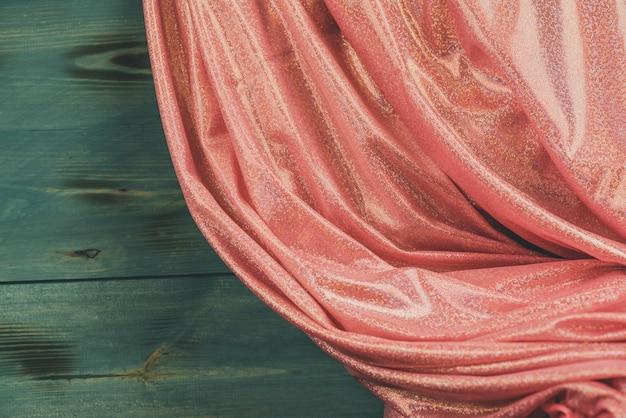 Glitter pailletten roze. roze glitter stof en hout groene achtergrond Premium Foto