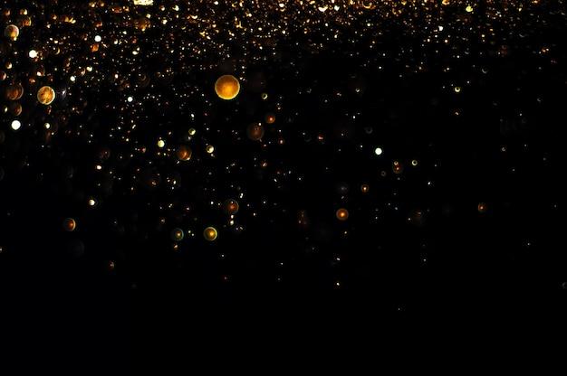 Glitter vintage lichten achtergrond. goud en zwart. de focus