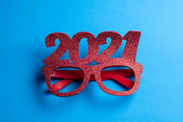 Glitterglazen met cijfers uit het jaar 2021 op een blauwe achtergrond