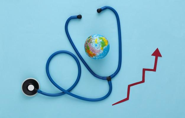 Globaal geneeskundeconcept. stethoscoop met wereldbol, groeipijl op blauw