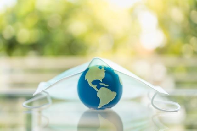 Global healthcare, coronavirus, covid-19 protection concept. sluit omhoog van miniwereldbal onder chirurgisch gezichtsmasker met groene aardachtergrond en exemplaarruimte.