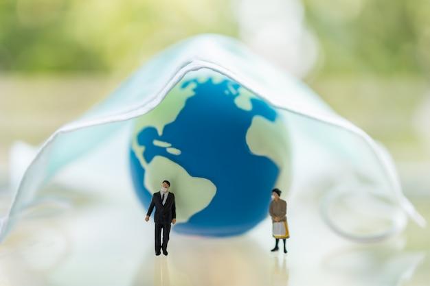 Global healthcare, coronavirus, covid-19 protection concept. zakenman en vrouwen miniatuurcijfermensen die gezichtsmasker dragen die zich met miniwereldbal bevinden en chirurgisch gezichtsmasker.