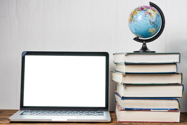 Globe en boeken in de buurt van de laptop