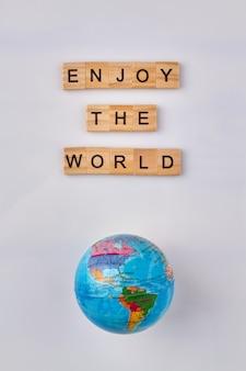 Globe en letterblokken. geniet van de wereld. motivatiecitaat op witte achtergrond.