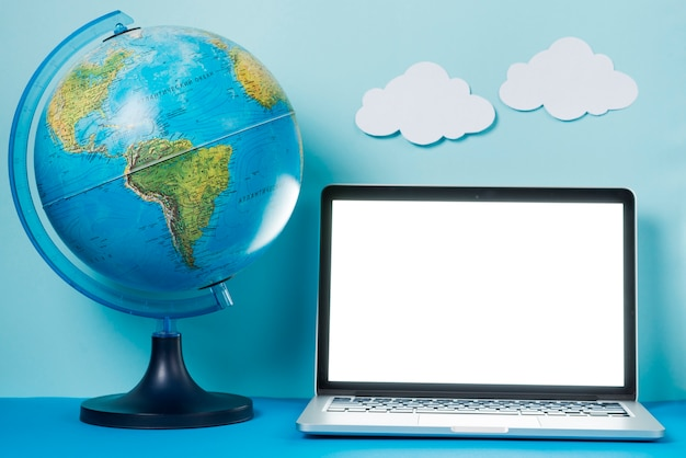 Globe en wolken in de buurt van de laptop