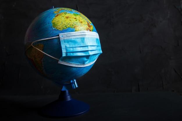Globe in een beschermend medisch masker. coronavirus valt de planeet aan.