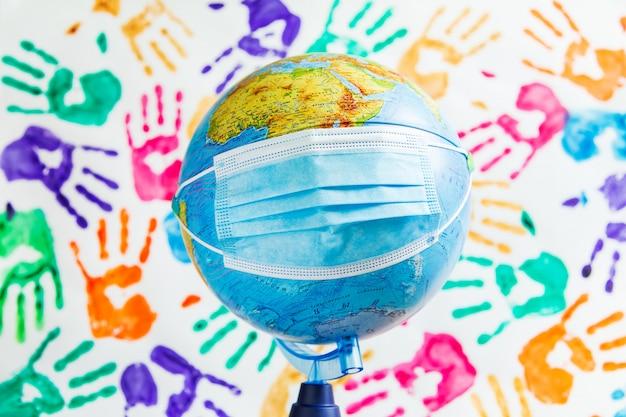 Globe in een beschermend medisch masker op de achtergrond van gekleurde handafdrukken.