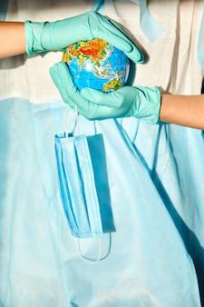 Globe in een medisch masker in de handen van de dokter bij hard licht