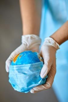 Globe in een medisch masker in de handen van de dokter