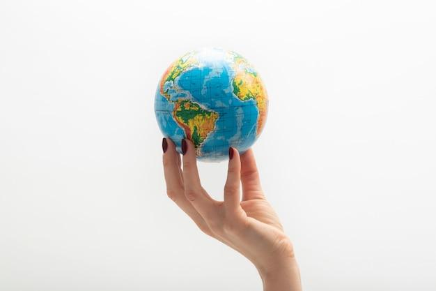 Globe op het puntje van de vingers van de vrouw. vrouwelijke hand houdt bol. wereld in mensenhanden. witte achtergrond.