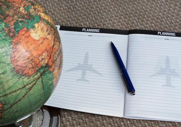 Globe, pen en notebook op tafel