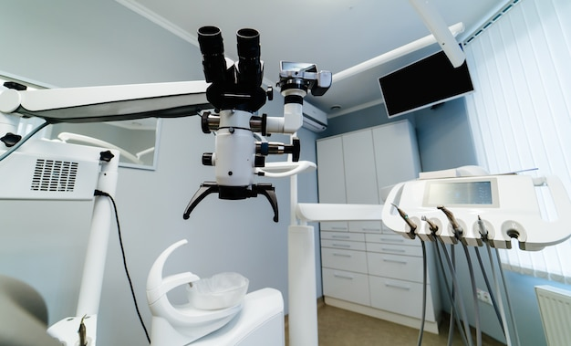 Gloednieuw medisch kantoor. tandarts kamer. stomatoloog professionele apparatuur. hi-tech medische kliniek. tandarts kliniek. modern tandartspraktijkbinnenland. geavanceerde microscoop voor tandbehandeling.