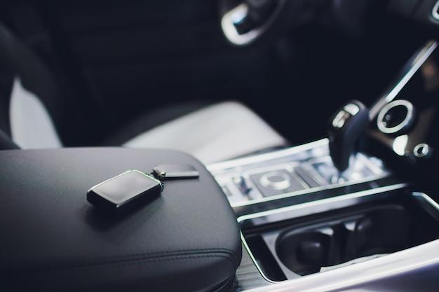 Gloednieuwe autosleutels op lederen close-up. auto-industrie concept.