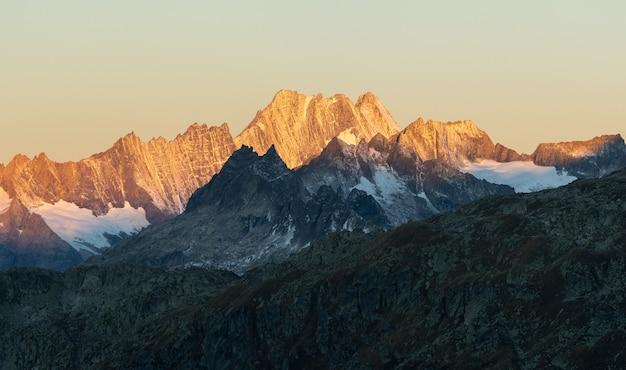 Gloeiende alpen in de zonsopgangtijd