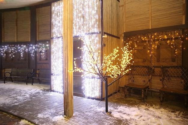 Gloeiende boom bij het huis op kerstavond