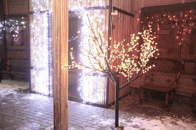 Gloeiende boom in de buurt van het huis op kerstavond. vakantie concept