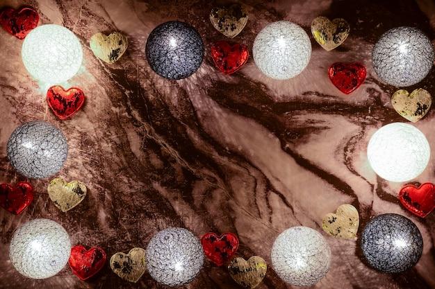 Gloeiende decoratieve ballen en verschillende harten liggen rond de omtrek op een marmeren achtergrond. er is een plek in het centrum voor inscripties voor verschillende feestdagen.