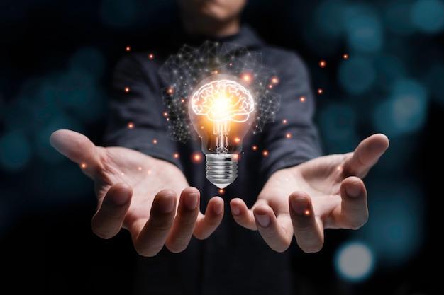 Gloeiende gloeilamp van de zakenmanholding met virtuele hersenen en oranje licht. creatief nieuw bedrijfsideeconcept.