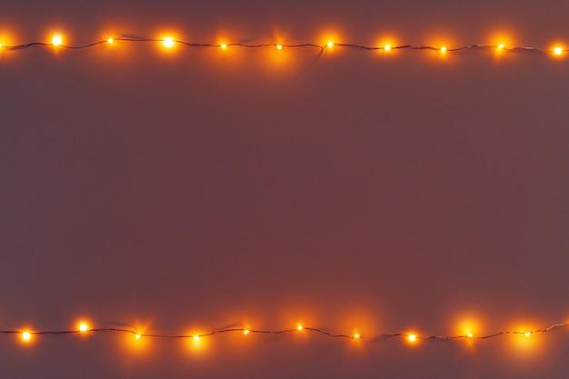 Gloeiende gouden elektrische garland op een grijze muur