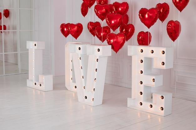 Gloeiende grote letters love met led retro lampen. rode luchtballen in vorm van hart