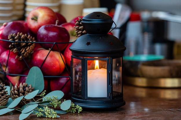 Gloeiende kaarslantaarn en mand met appels op de tafel in de kerstmarkt in riga, letland