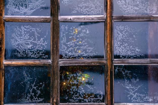 Gloeiende kerstboom nauwelijks zichtbaar achter het bevroren vensterglas met ijzige patronen
