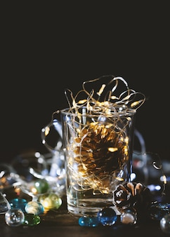 Gloeiende kerstmislichten en gouden denneappel in een glaskruik, de achtergrond van de kerstmisdecoratie.