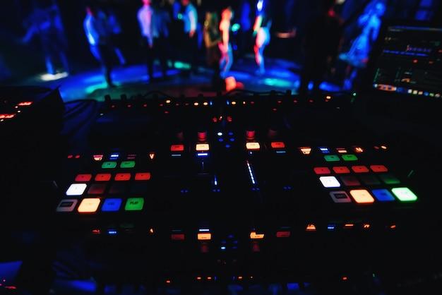 Gloeiende knoppen professioneel bord voor mixen en muziek op feestje in nachtclub