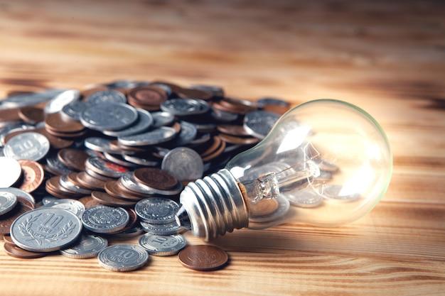 Gloeiende lamp en munten op een donkere scène