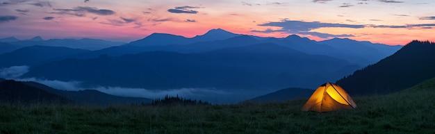 Gloeiende oranje tent in de bergen onder dramatische avondlucht