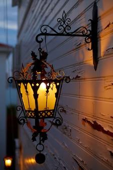 Gloeiende oude straatlantaarnverlichting op de gevel van het huis. schemering op de straat van de oude stad.